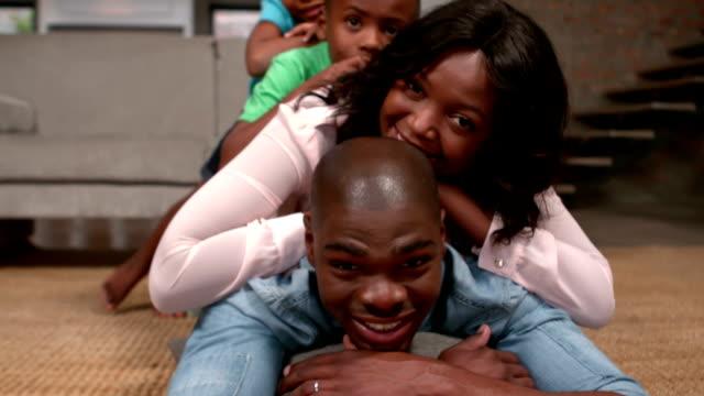 Family posing on floor for camera video