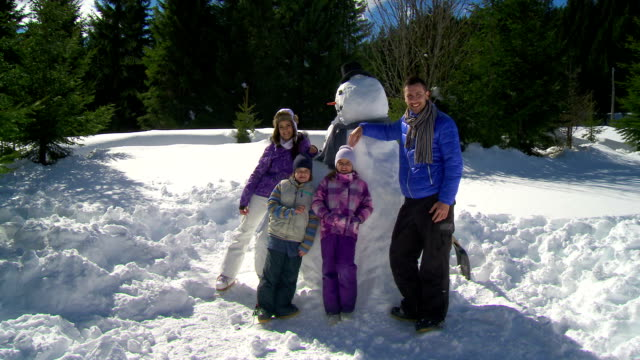 HD CRANE: Family Posing With A Snowman HD1080p: CRANE shot of a young family posing with a snowman in the snow covered countryside. snowman stock videos & royalty-free footage