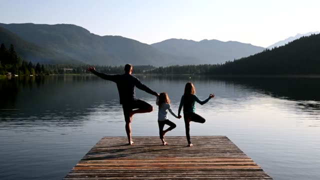 family practising yoga outdoors - mindfulness стоковые видео и кадры b-roll