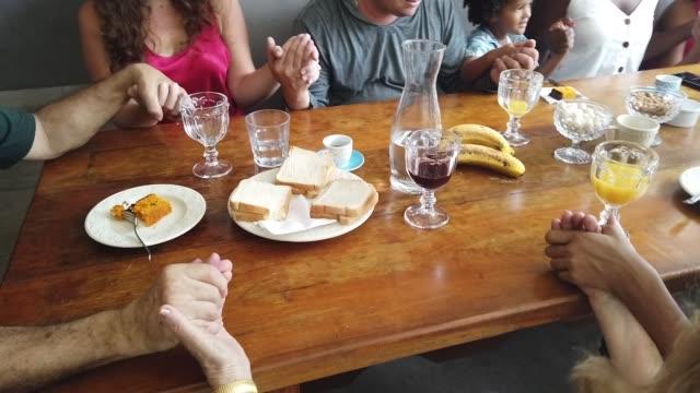 familie betet vor dem frühstück - dankbarkeit stock-videos und b-roll-filmmaterial