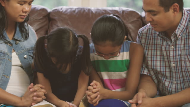 Family praying together during devotionals video