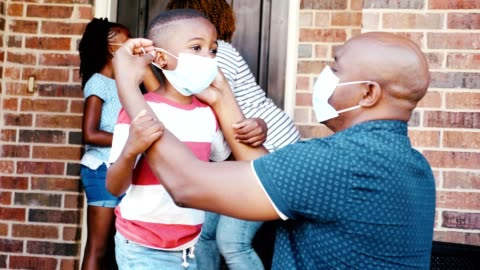 Family prepare to leave home during the COVID-19 pandemic A mid adult dad carefully places a protective face mask on his young son as they leave their house during the COVID-19 pandemic. The man's wife is helping their daughter put on a face mask in the background. child stock videos & royalty-free footage