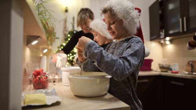 vídeos de stock e filmes b-roll de family preparing and baking christmas cakes - christmas cooking