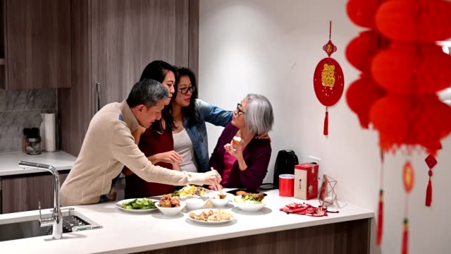 Family preparing for Chinese New Years Chinese New Years celebrations. Family having dinner. Bonding over family traditions. chinese new year stock videos & royalty-free footage