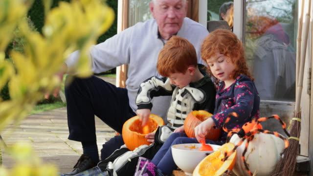 family pumpkin carving - incisione oggetto creato dall'uomo video stock e b–roll