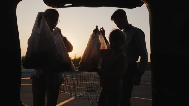 Family puts shopping bags from supermarket in car boot video