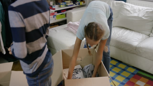 vídeos de stock e filmes b-roll de family putting clothes for reuse into boxes - economia circular