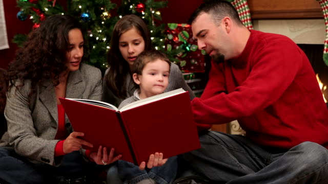Family reading Christmas book together video