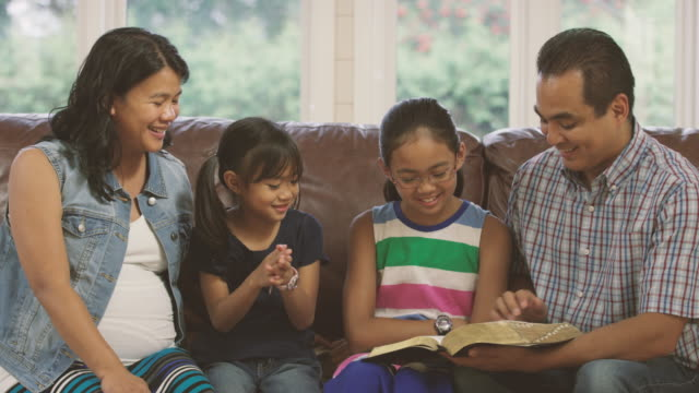Family reading the bible and praying together at home video