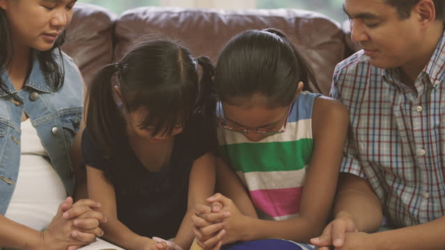 vídeos de stock e filmes b-roll de family reading the bible and praying together at home - igreja