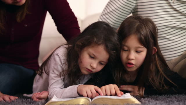 family reading the bible together - nipote femmina video stock e b–roll