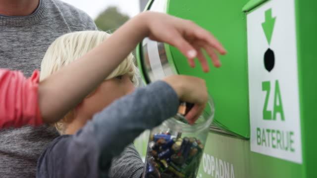 vídeos de stock e filmes b-roll de family recycling old batteries - economia circular