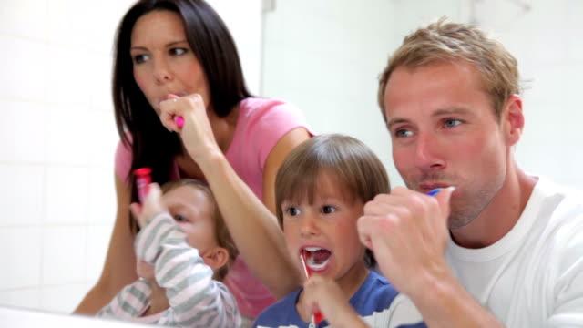 famiglia riflettono in bagno, lavarsi i denti specchio - trentenne video stock e b–roll