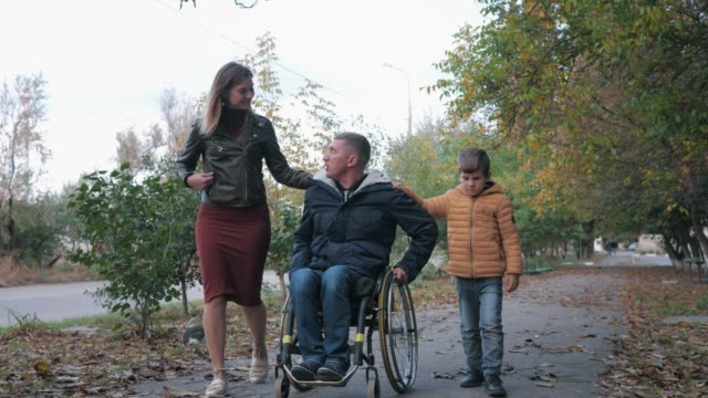 familjerelationer, lycklig fader funktionshindrade person i en rullstol promenader med sin glada familj längs höst gatan - fysiskt funktionshinder bildbanksvideor och videomaterial från bakom kulisserna