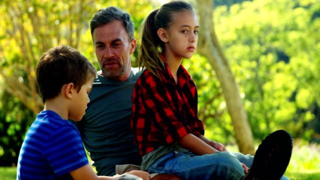 Family relaxing in park 4k video