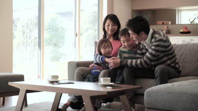 ご家族とのリラックスしたリビングルームにはソファー - 家族 日本人点の映像素材/bロール