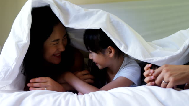 Family relaxing together under a blanket in bedroom 4k video