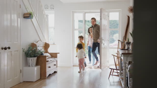 Family Returning Home After Trip Out With Excited Children Running Ahead