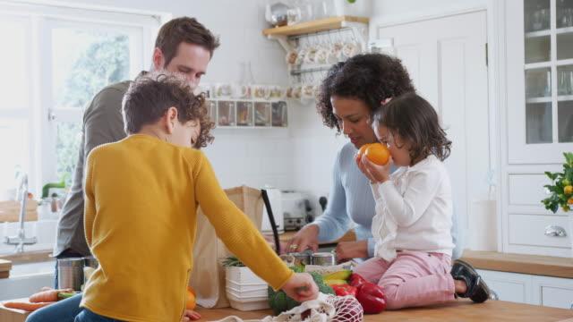 familj återvänder hem från shopping resa med plast gratis påsar uppackning livsmedel i köket - bära bildbanksvideor och videomaterial från bakom kulisserna