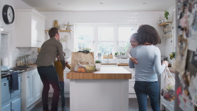 family returning home from shopping trip using plastic free bags unpacking groceries in kitchen - borsa della spesa video stock e b–roll