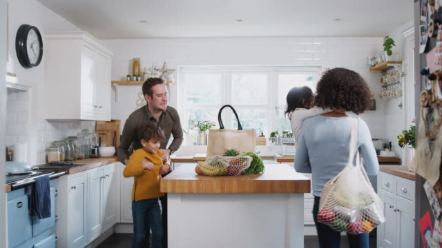 family returning home from shopping trip using plastic free bags unpacking groceries in kitchen - kitchen room video stock e b–roll