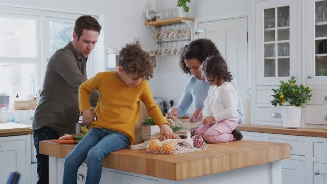 famiglia di ritorno a casa dal viaggio di shopping utilizzando sacchetti plastici gratuiti disimballando generi alimentari in cucina - grocery home video stock e b–roll