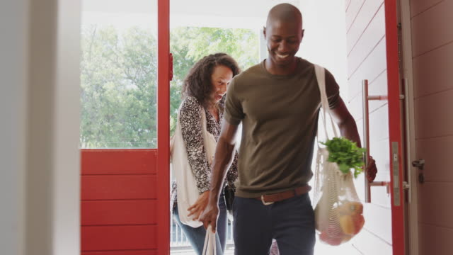 familj återvänder hem från shopping resa med plast gratis livsmedels butiker väskor öppna ytterdörren - ytterdörr bildbanksvideor och videomaterial från bakom kulisserna