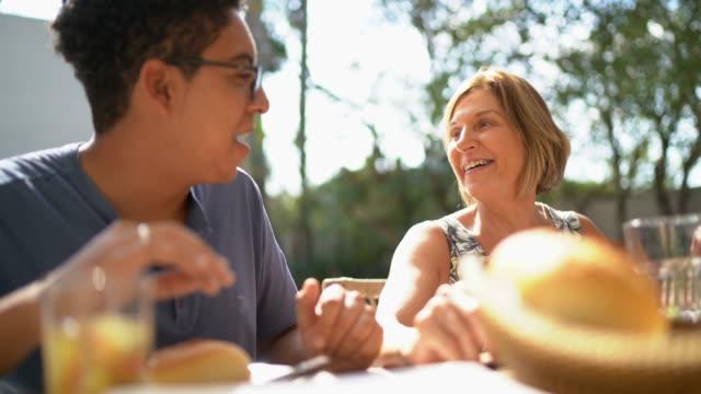 familie wieder beim essen grill - teenage friends sharing food stock-videos und b-roll-filmmaterial