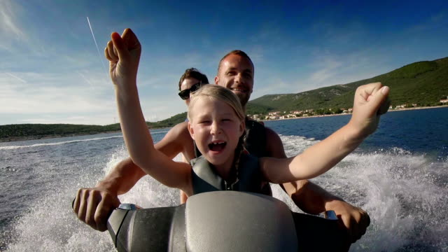 POV Family Riding A Jet Boat HD1080p: POV WIDE shot of a family having fun riding a personal watercraft/water scooter on the sea. holiday stock videos & royalty-free footage