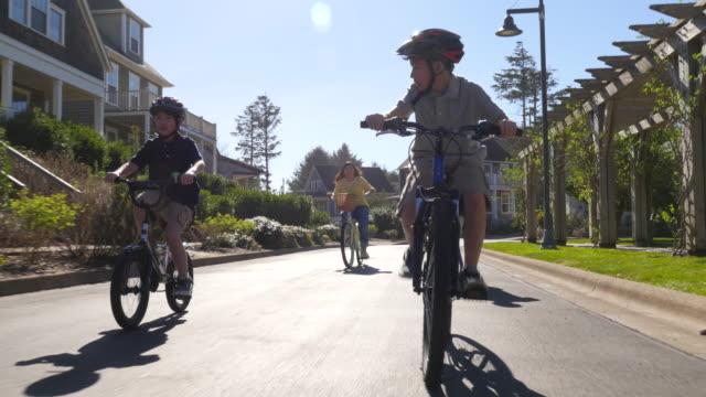 familjen ridning cyklar i kustsamhälle - samhörighet bildbanksvideor och videomaterial från bakom kulisserna