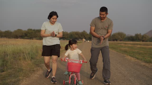 Family riding bikes on sunny summer day