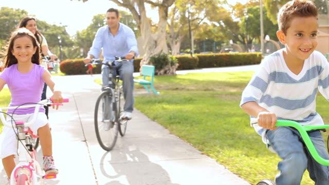 Family Riding Bikes Through Summer Park video