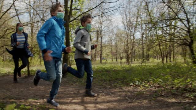 vídeos de stock e filmes b-roll de family running in forest during covid-19 pandemic - atividade recreativa