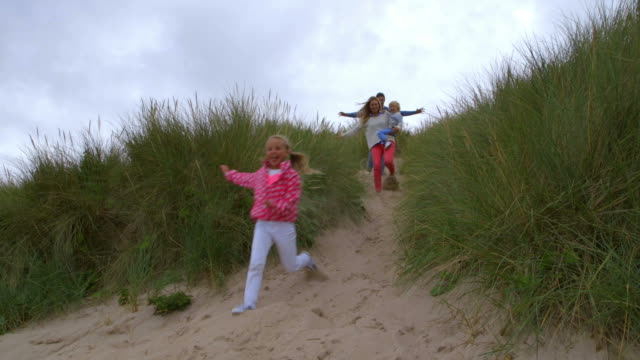 Family Running Through Sand Dunes In Slow Motion Together video
