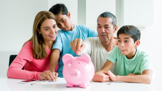 familie geld zu sparen in ein sparschwein - sparsamer lebensstil stock-videos und b-roll-filmmaterial