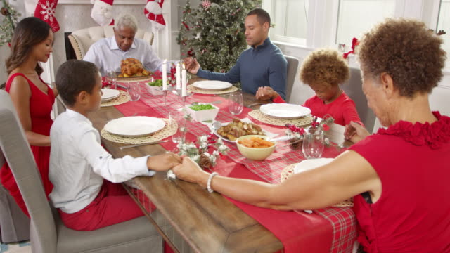 Family Saying Grace Before Christmas Meal Shot On R3D video