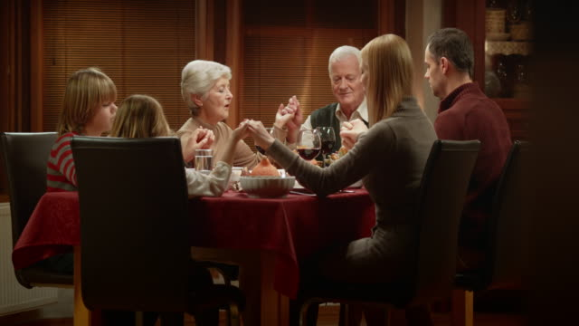 Family saying grace together at the Thanksgiving table before dinner video