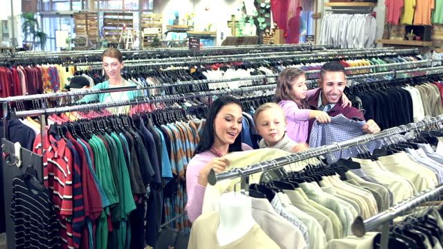 stockvideo's en b-roll-footage met familie winkelen in kledingwinkel met kinderen - discountwinkel