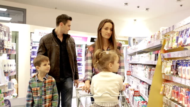Family shopping in supermarket, panning shot video