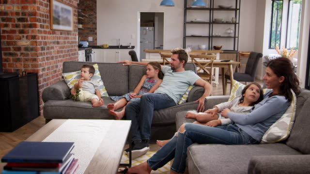 Family Sit On Sofa In Open Plan Lounge Watching Television Family Sit On Sofa In Open Plan Lounge Watching Television family watching tv stock videos & royalty-free footage