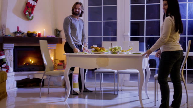 Family sits at the festive christmas table Woman brings salad and put it on the table. Father invites daughters to a festive table. Happy family celebrates christmas evening at the festive table with delicious food. human relationship stock videos & royalty-free footage
