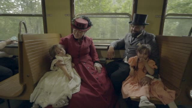 Family sitting and talking on a moving steam train car Victorian family visiting old train station 19th century style stock videos & royalty-free footage