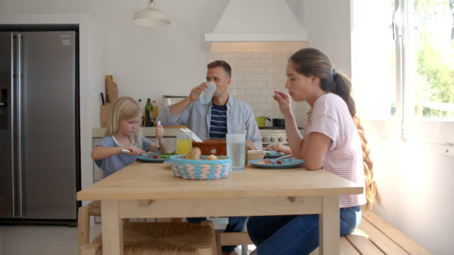 Famille assis autour de la table de cuisine déjeuner - Vidéo