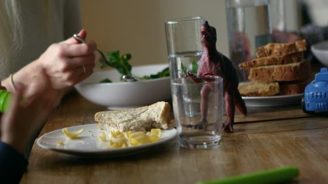 Famille s'asseyant à la table de cuisine et mangeant le repas tourné sur - Vidéo