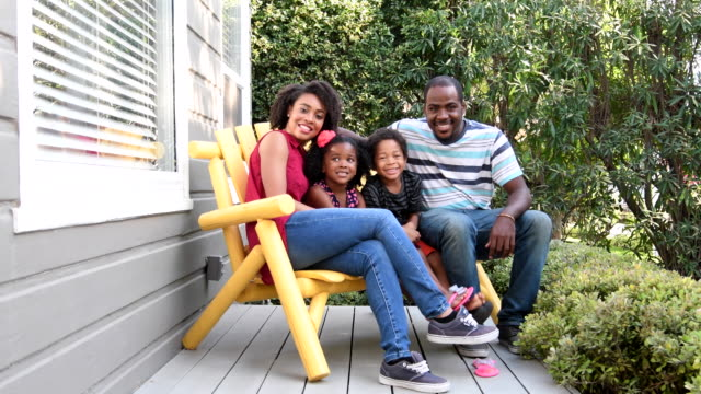 Family sitting on bench on porch smiling The two children are sitting between their parents and looking at the camera laughing and smiling. porch stock videos & royalty-free footage