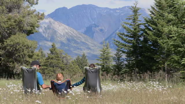 Family sitting on camping chairs holding hands and looking at mountains in Banff National Park in Summer.