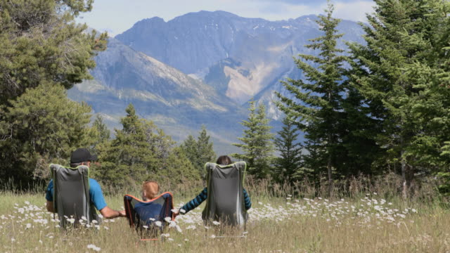 Video Family sitting on camping chairs holding hands and looking at mountains in Banff National Park in Summer.