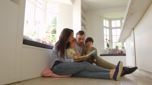 Family Sitting On Floor Reading Story At Home Shot On R3D video