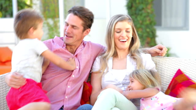 Family Sitting  On Garden Seat Together video