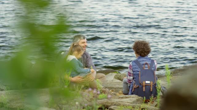 family sitting on rocks by lake and talking - four seasons filmów i materiałów b-roll